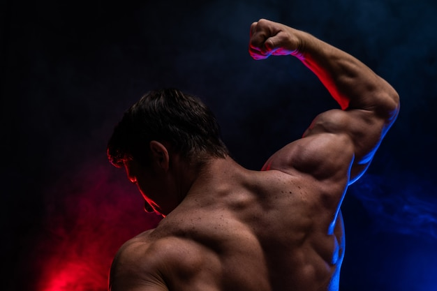 Homem musculoso mostrando músculos isolados no fundo preto close-up