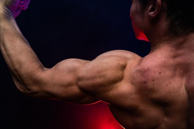 Homem musculoso mostrando músculos isolados no fundo preto estilo de vida saudável
