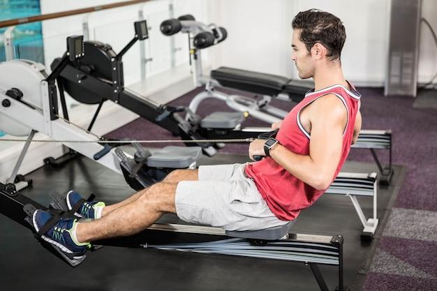 Homem musculoso na máquina de remo no ginásio