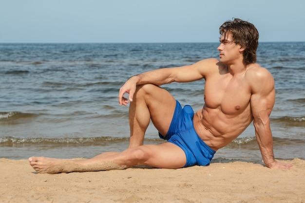 Homem musculoso na praia