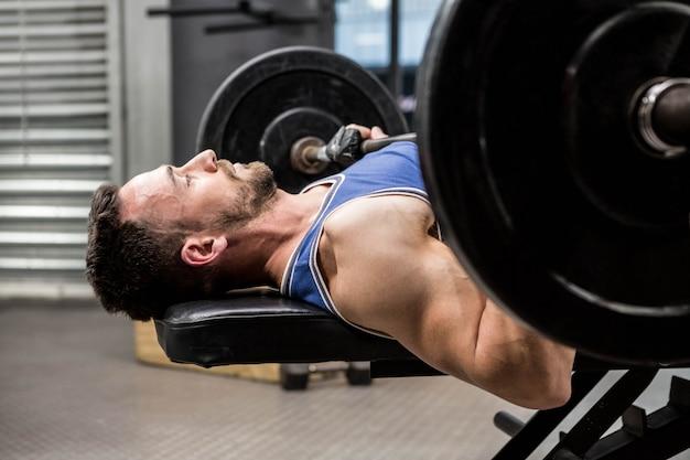 Homem musculoso no banco, levantando a barra no ginásio crossfit