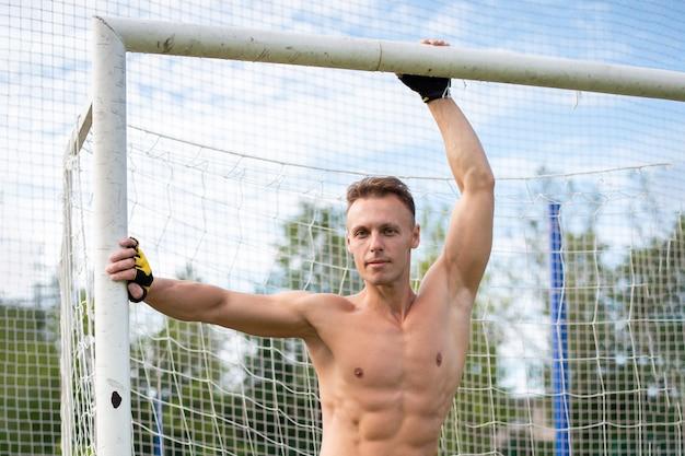 Homem musculoso no campo de futebol, perto do poste da baliza. para qualquer propósito.