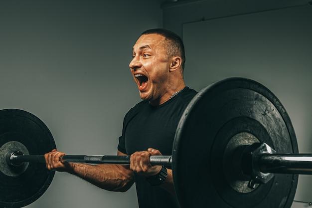 Homem musculoso no sportswear preto, levantando a barra em uma academia