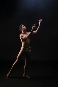 Homem musculoso nu em pé e levantando as mãos