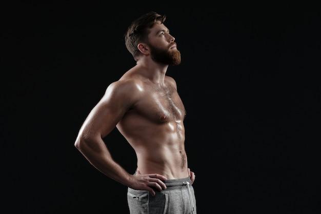 Homem musculoso nu em seu perfil. fundo escuro isolado