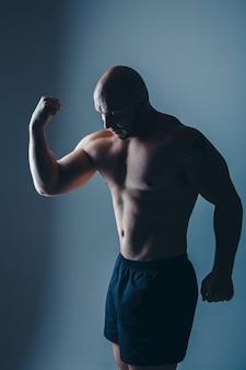Homem musculoso nu forte mostra seus músculos