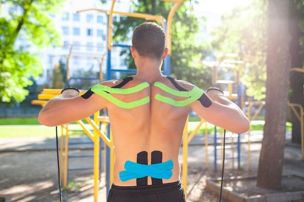 Homem musculoso nu treinando com corda de fitness em campo esportivo