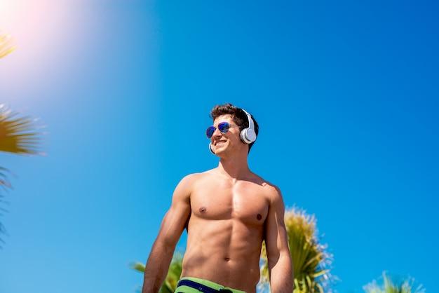 Homem musculoso, ouvindo música em fones de ouvido wile malhando