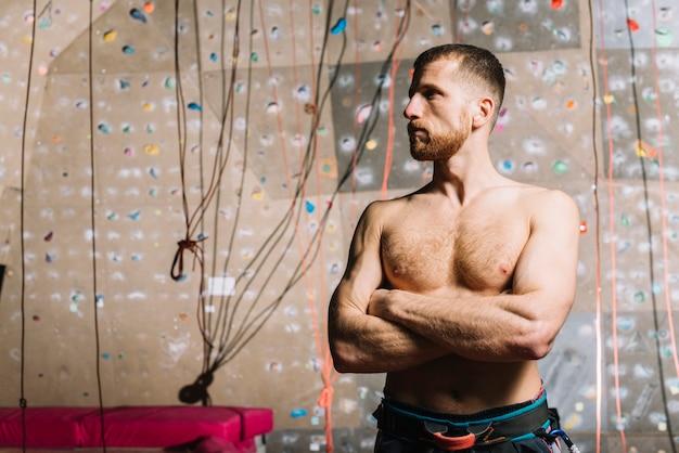 Homem musculoso perto de parede de escalada