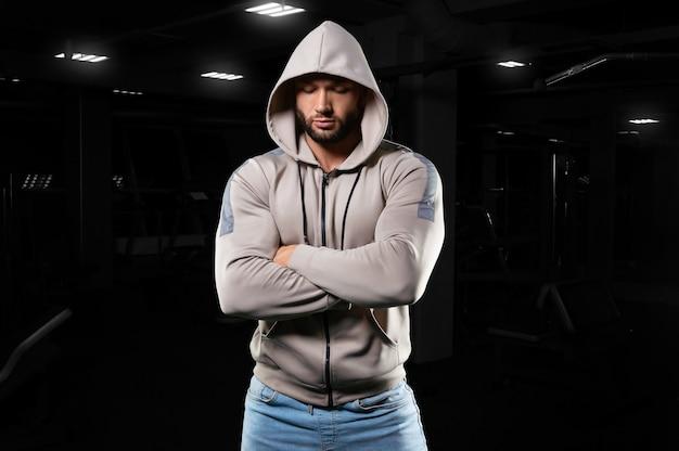 Homem musculoso posa no ginásio de jeans e moletom