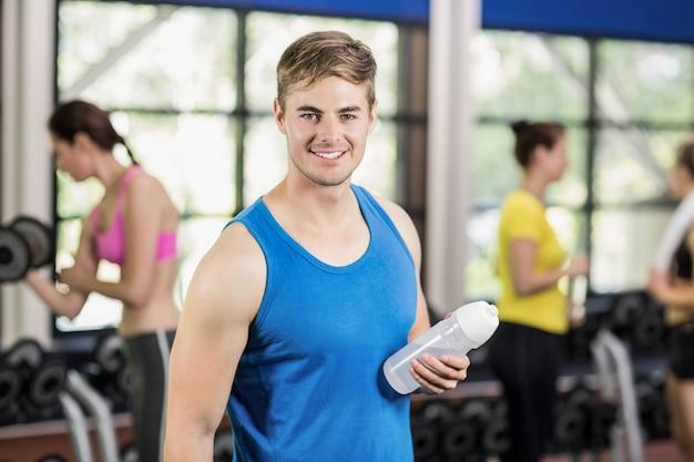 Homem musculoso posando com mulheres atléticas para trás no ginásio