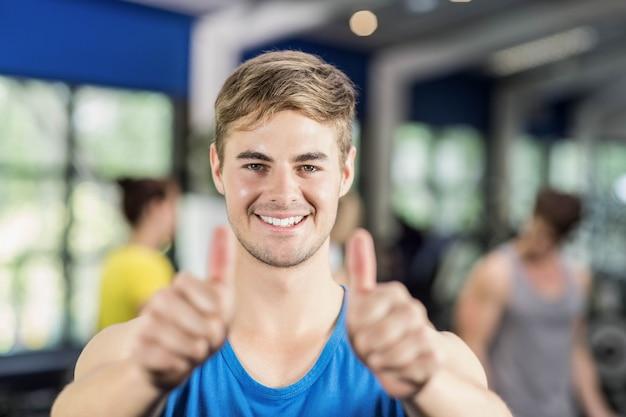 Homem musculoso posando com polegares para cima no ginásio