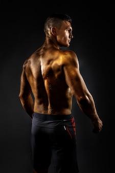 Homem musculoso, posar, vista lateral, cena preta