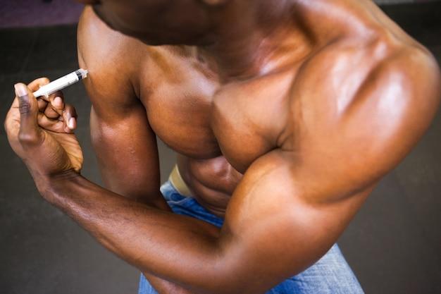 Homem musculoso sem camisa injetando esteróides