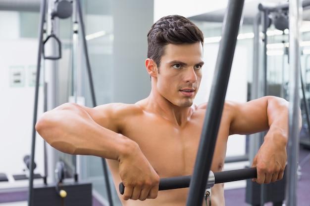 Homem musculoso sem camisa, usando o bíceps puxe na academia
