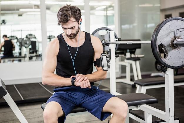 Homem musculoso sentado no banco de barra e usando smartwatch no ginásio