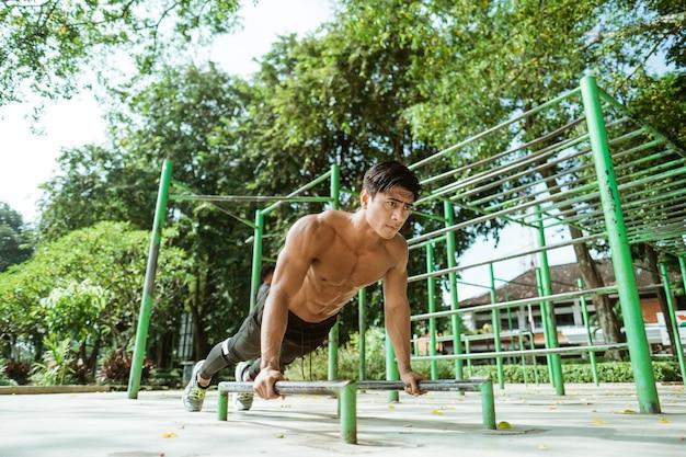 Homem musculoso sexy fazendo movimento de flexão mostra seus braços musculosos ao se exercitar ao ar livre no parque
