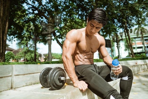 Homem musculoso sexy sentado em poses segurando uma garrafa perto de halteres enquanto se exercita ao ar livre no parque