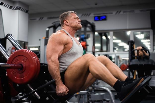 Homem musculoso treina as pernas no ginásio.