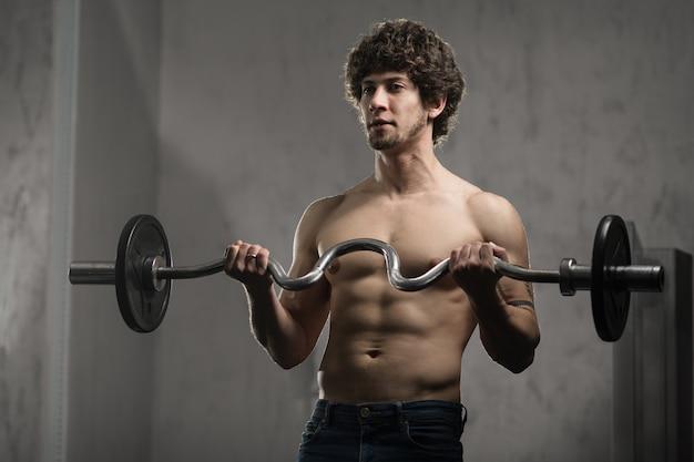 Homem musculoso treina bíceps com barra no ginásio