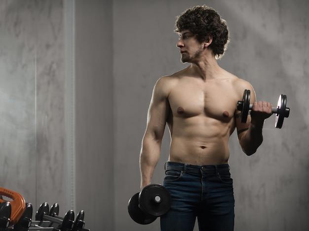 Homem musculoso treina halteres de bíceps no ginásio, treinamento de mão