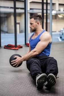 Homem musculoso treino com bola de exercício no ginásio
