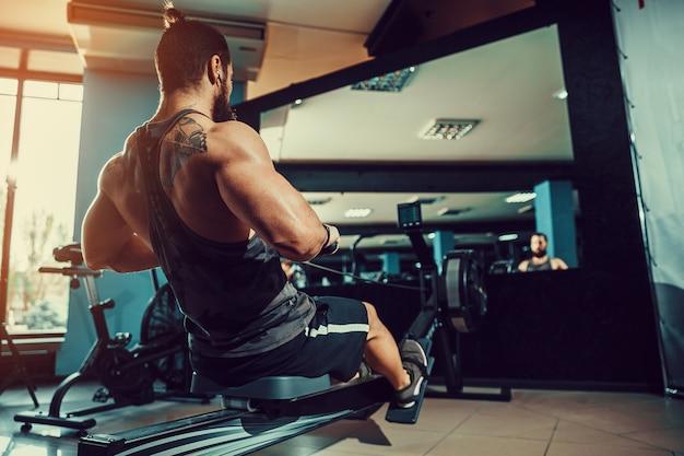 Homem musculoso, usando a máquina de remo no ginásio