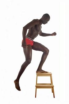 Homem musculoso vestindo apenas cueca vermelha.