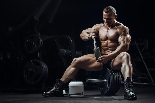 Homem na academia com frasco de proteína em pó