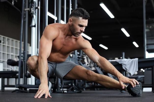 Homem na academia fazendo exercícios de alongamento no chão.