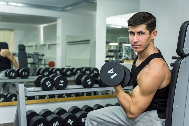Homem na academia segurando halteres de perto