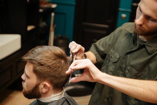 Homem na barbearia cortando cabelo de cabeleireiro com uma tesoura enquanto está sentado na cadeira.