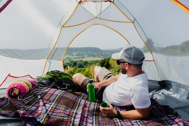 Homem na barraca, relaxando e olhando a natureza