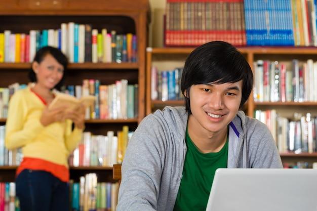Homem na biblioteca com laptop