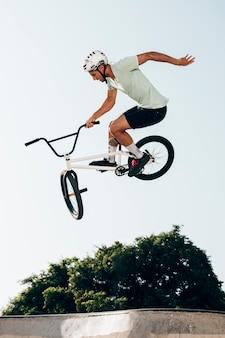 Homem na bicicleta, executando truques no skatepark