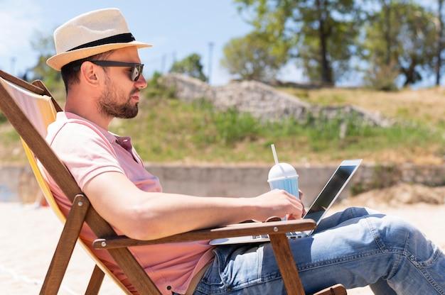 Homem na cadeira de praia, trabalhando no laptop enquanto toma uma bebida