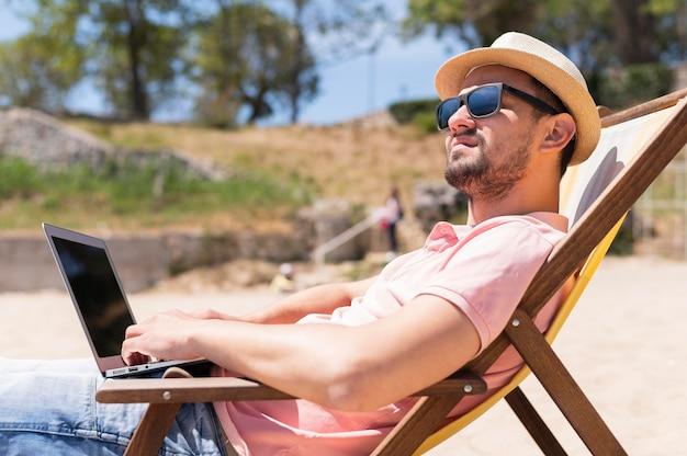 Homem na cadeira de praia, trabalhando no laptop