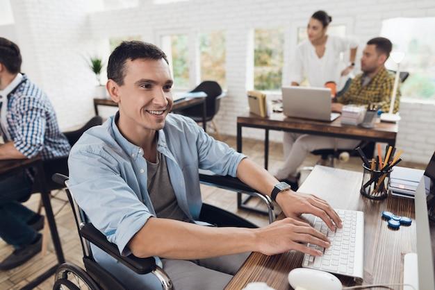 Homem na cadeira de rodas que trabalha no computador no escritório.
