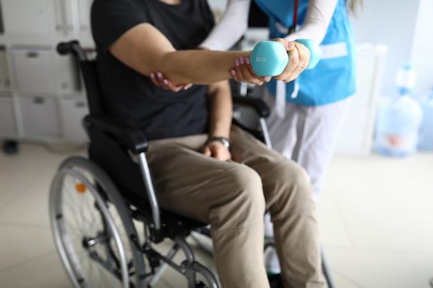 Homem na cadeira de rodas trabalha a mão com halteres