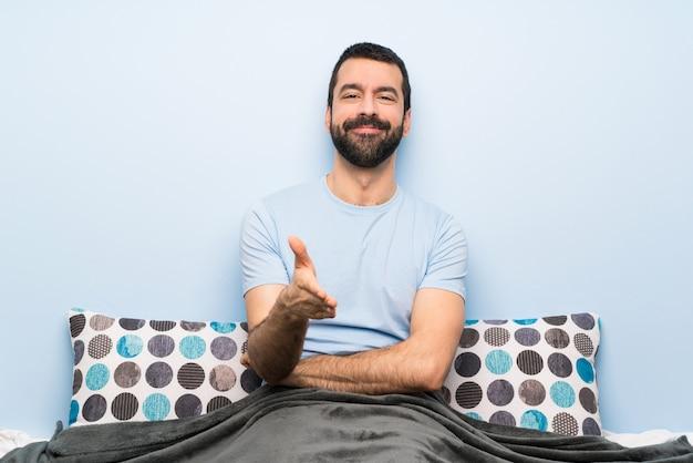 Homem na cama apertando as mãos para fechar um bom negócio