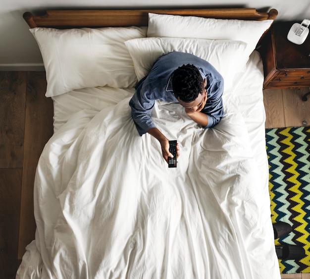 Homem na cama assistindo uma tv