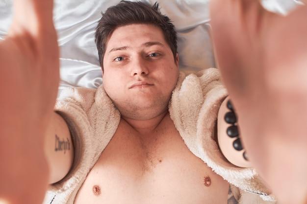 Homem na cama branca acorda se espreguiçando, high key, close-up