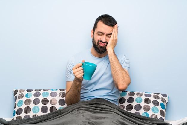 Homem na cama com barba segurando uma xícara de café