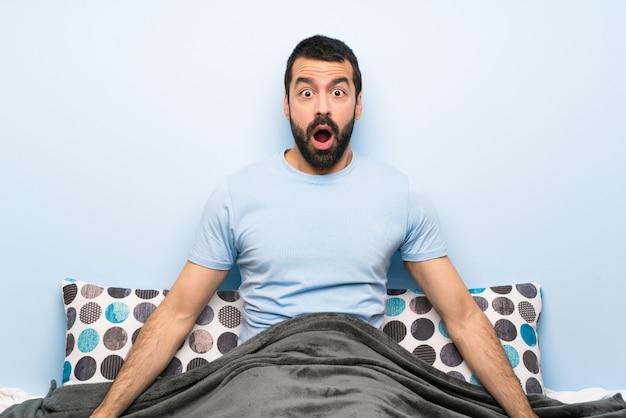Homem na cama com expressão facial de surpresa