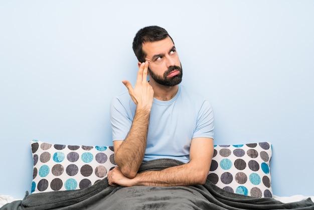 Homem na cama com problemas fazendo gesto de suicídio