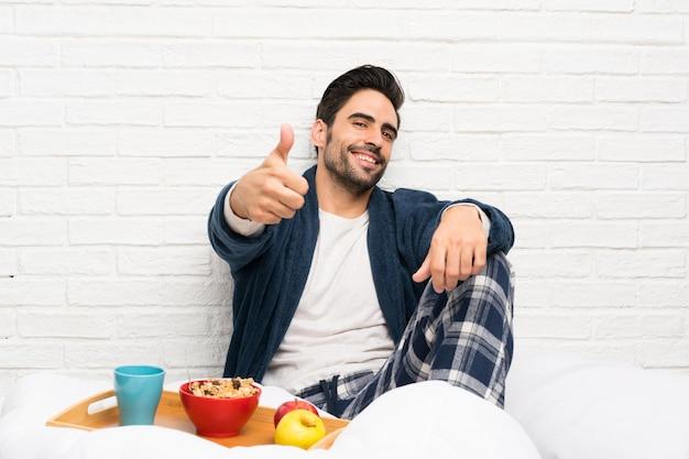 Homem na cama com roupão e tomando café da manhã com os polegares para cima porque algo de bom aconteceu