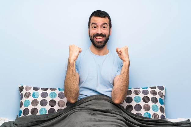 Homem na cama comemorando uma vitória na posição de vencedor