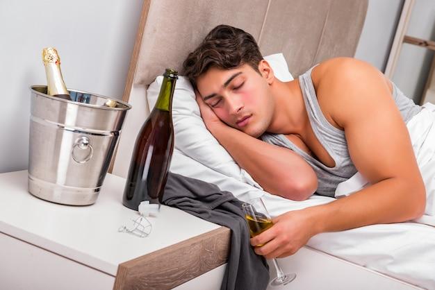 Homem na cama depois da festa - conceito de ressaca