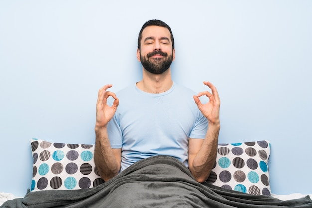Homem na cama em pose de zen