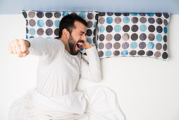 Homem na cama em vista superior bocejando